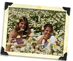 Dani and Jessi sitting together in field of daisies.